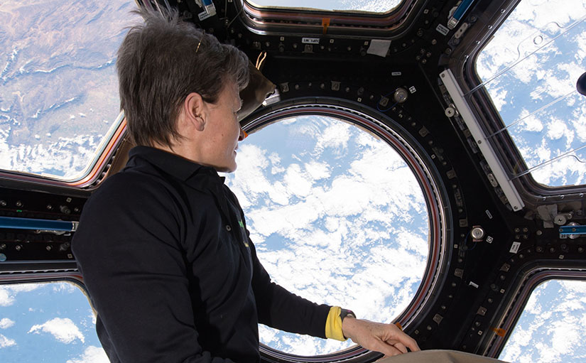 An astronaut views clouds from a window in space.