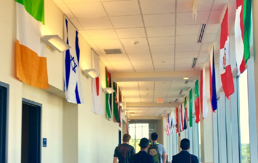 A view of international flags lining a hallway. Four young men walk down the hallway with their backs turned to us.