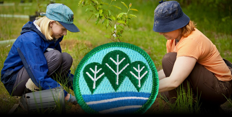 Composite image of Girl Scouts planting a tree overlaid with the badge earned